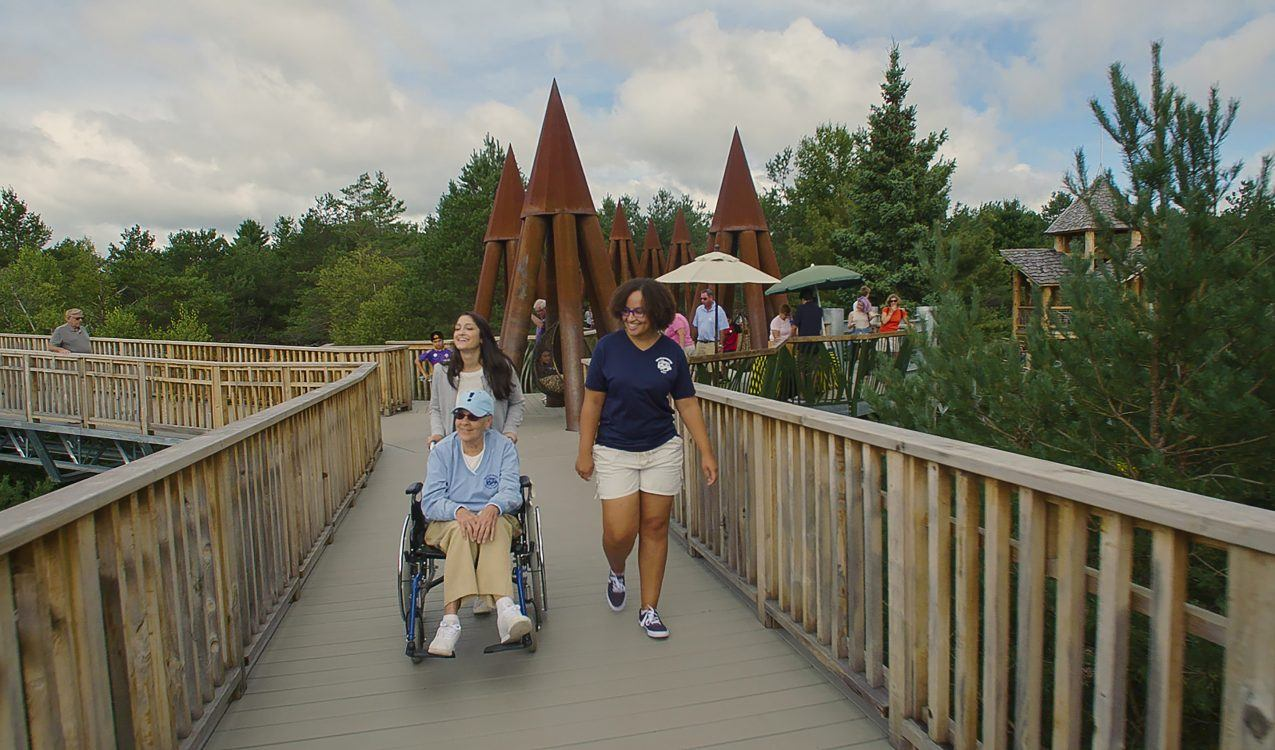 Woman in wheelchair on The WIld Center's Wild Walk.